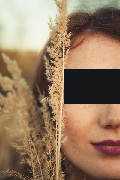 a woman with a black rectangle over her eyes