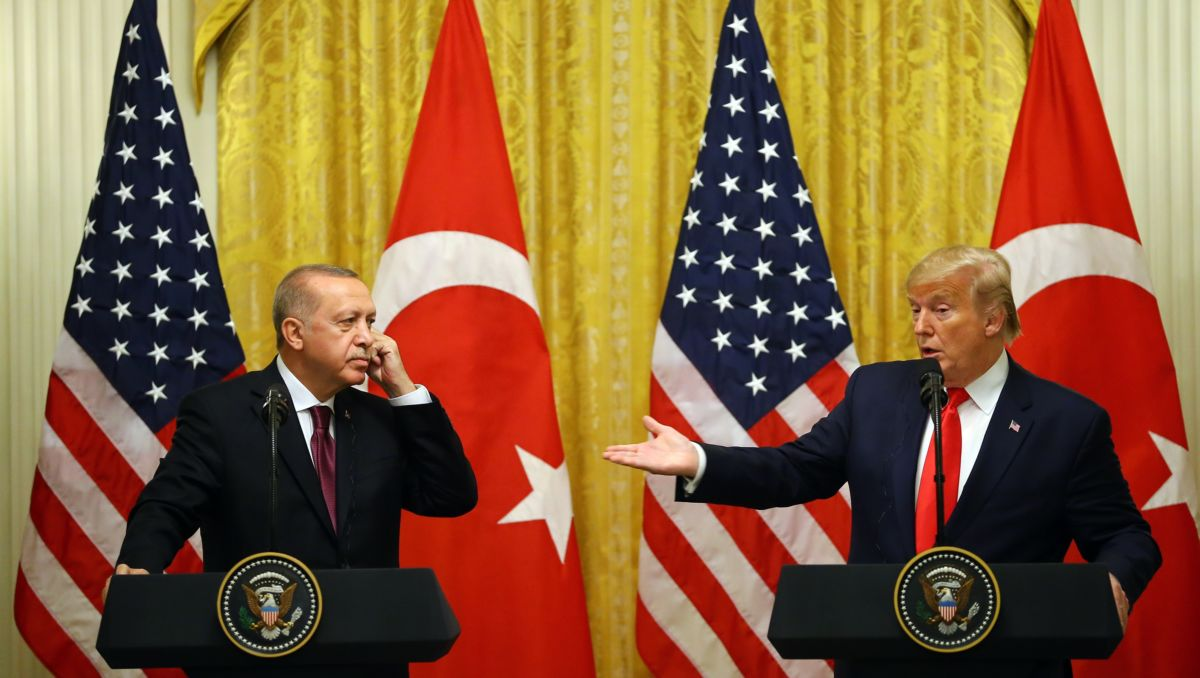 Donald Trump gestures at Tayyip Erdogan as they both stand at podiums
