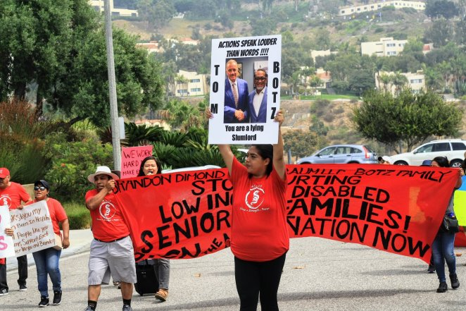 A woman in red displays a sign decrying Tom Botz as a slumlord