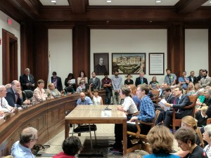 Max Shannon, Madeleine Lombard, and Aislyn Jewett testifying about climate legislation to a packed room at the MA State House.