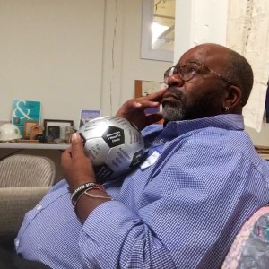 Pastor Louis Mitchell sitting on a couch holding a silver and black soccer ball with text written on it.