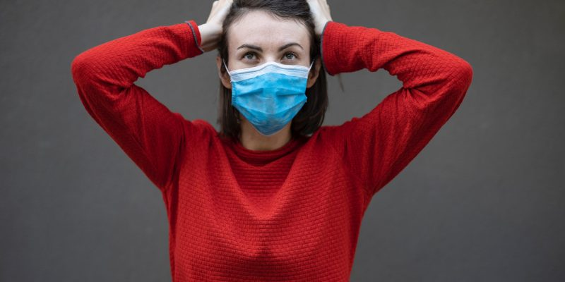 woman in red sweater with face mask