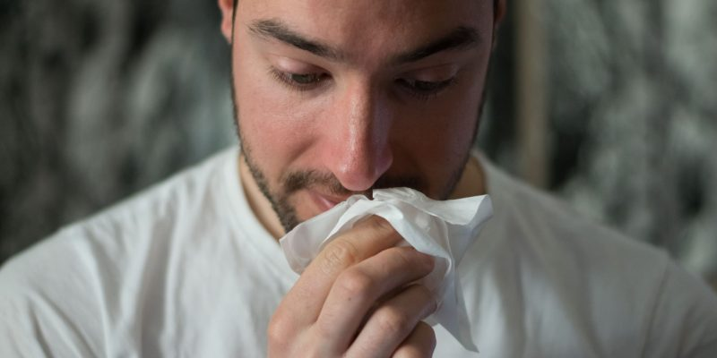 man wiping mouth with tissue paper