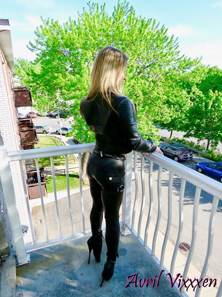 avrilvixxxen stands outside on the balcony in a latex BDSM bodysuit and tall ballet boots.