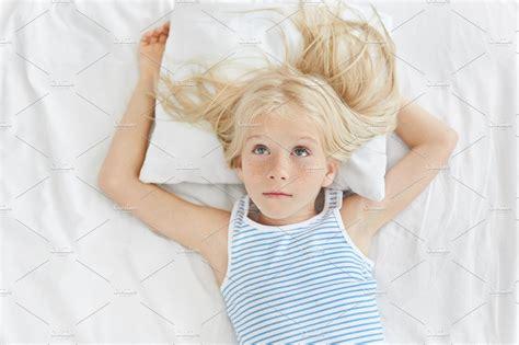 thoughtful girl long blonde hair wearing striped shirt
