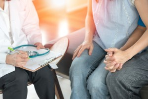 man and woman talking to doctor about infertility options