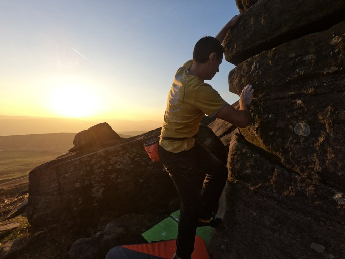 John climbing in front of a sunset. he is feeling for a foothold,