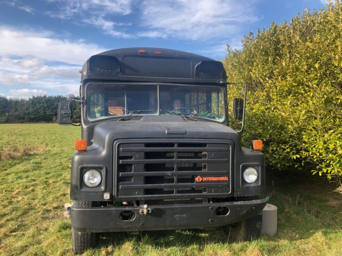 A view of the front of the bus. It has huge wheels and a massive grill. Lauren's head can be seen through the window. The bus is painted black.