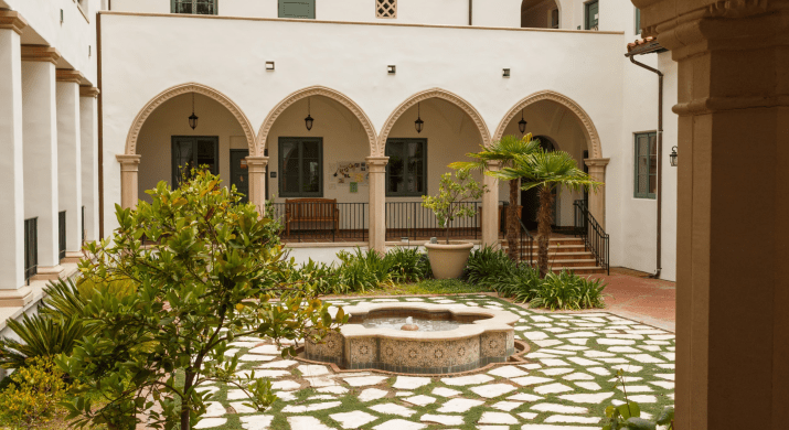 A fountain sits in the middle of a patio surrounded by plants, white stucco walls and arches.