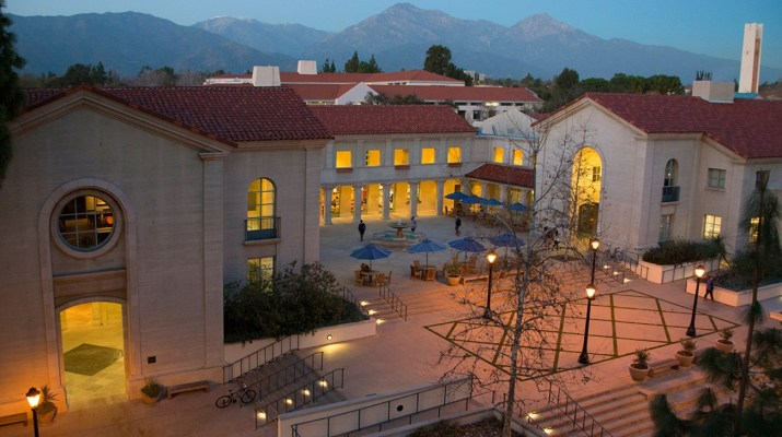 The Smith Campus Center, a tan building with a red roof, is pictured. Mountains and a clocktower can be seen in the background.