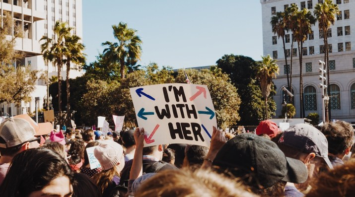 Taken at a protest, person holding a poster with 'I'm with Her' written on it and but and pink arrows pointing outwards.