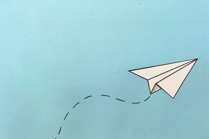 a paper airplane flies through the air over a blue background