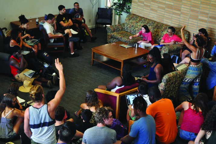 Pomona College Dean of Students Miriam Feldblum and students are sitting in Walker Lounge. Two people in frame, one in the bottom left and the other on the top right, have raised their hands.
