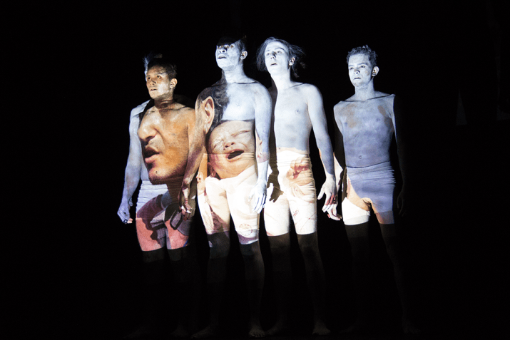 Four shirtless people stand on a dimly lit stage