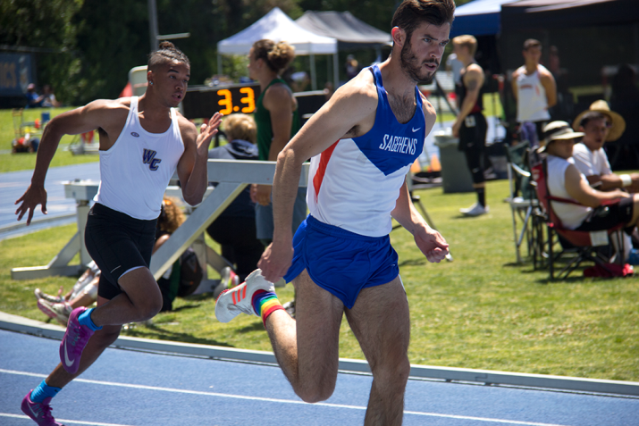 A man in track uniform sprints down a straight away