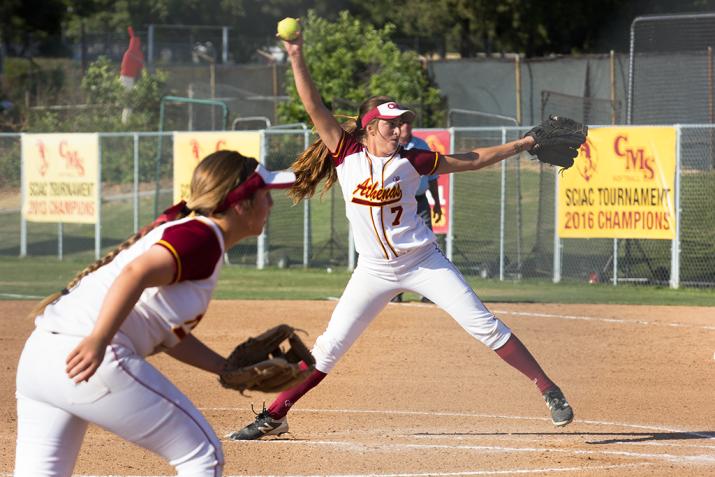 A softball player throws a softball