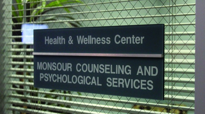 "a nameplate that reads ""health and wellness center"" and another below reading ""monsour counseling and psychological services"" on a door."