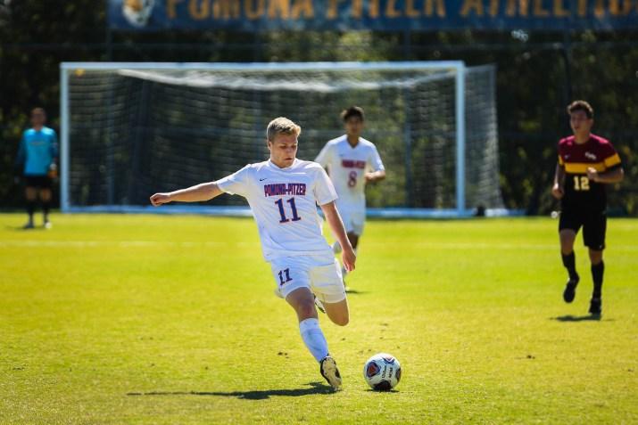A male soccer player kicks the soccer ball