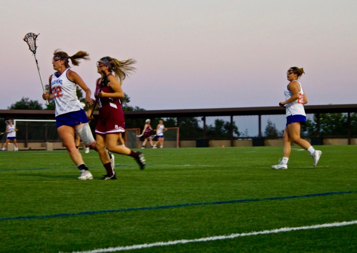 Three lacrosse players run across a field