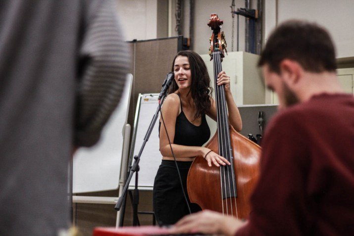 A woman sings and plays upright bass