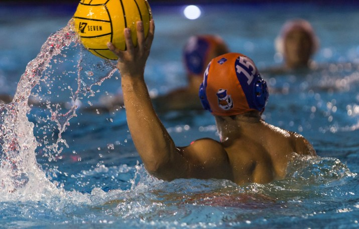 A male waterpolo player throws the ball in the pool