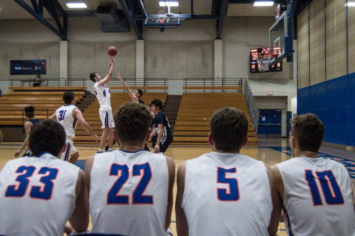 Sagehens players on the bench (with jersey numbers 33, 22, 5 and 10) watch in anticipation as a teammate shoots against the Life Pacific Warriors Nov. 28.