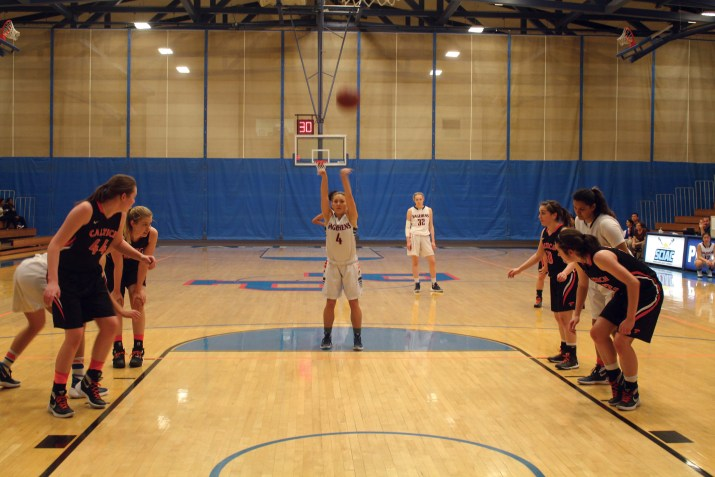 A female basketball player shoots a free throw