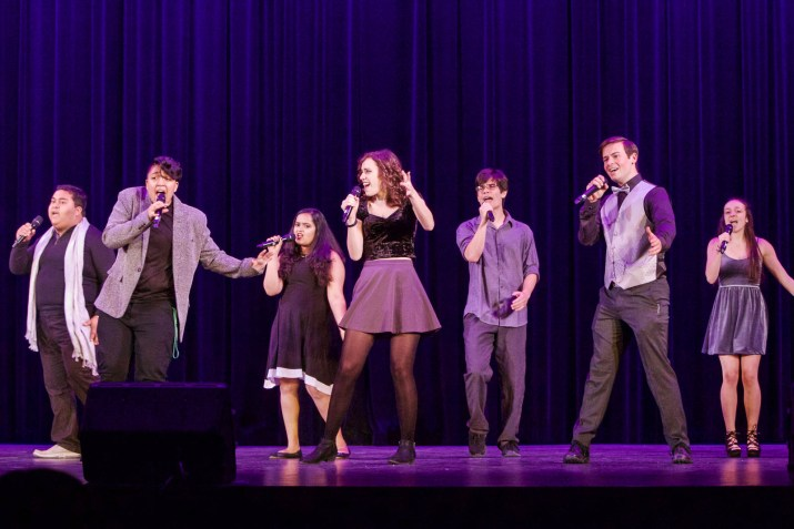 A group of students sings onstage