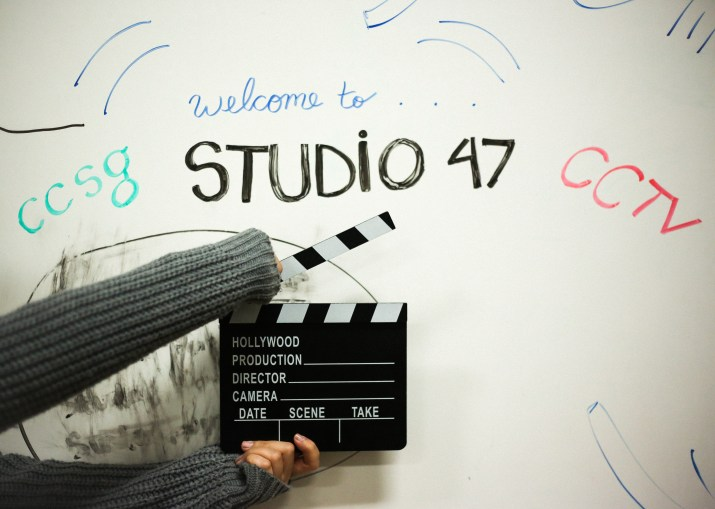 """A whiteboard that says """"welcome to studio 47"""" and an action clapboard"""