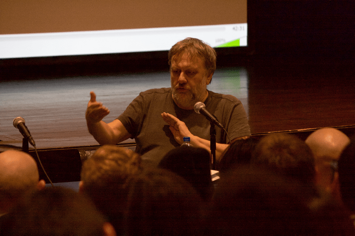 A man in a gray shirt talks into a microphone in front of a group of people in the audience