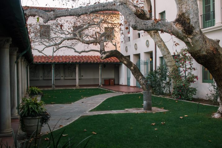 A green lawn with a walking path in front of a white building