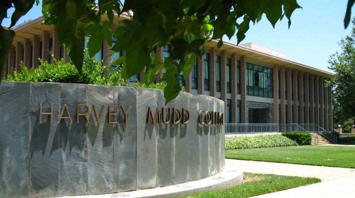 Gray concrete wall with Harvey Mudd College and building in the background.