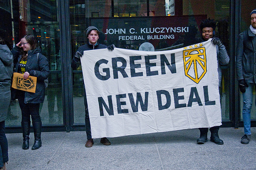 "Two people hold a sign reading ""Green New Deal"" in front of a building. The building has a sign reading ""John C. Kluczynski Federal Building."""