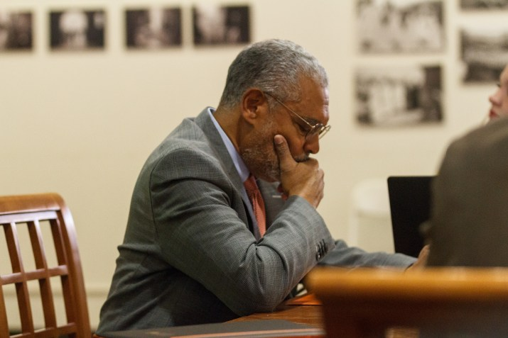 Melvin Oliver, a Black man with grey hair and eyeglasses, sits a table, looking at his hands. He is wearing a grey suit with a blue shirt and an orange tie.