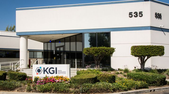 A Keck Graduate Institute building with a sigh in from of it displaying the KGI name and logo.