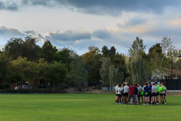The Claremont College's Lions rugby team huddles up on the field during a practice as the sun sets in the background.