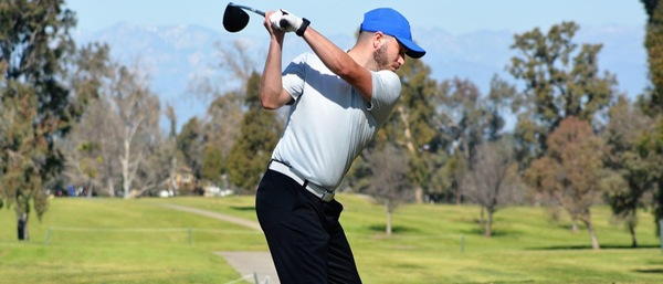 A golf player in a blue hat swings his club.