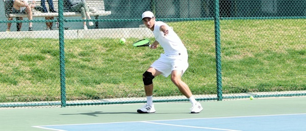 Jed Kronenberg PO '21 wears all white, except for a black knee brace on his right knee, and swings his tennis racket at the tennis ball.