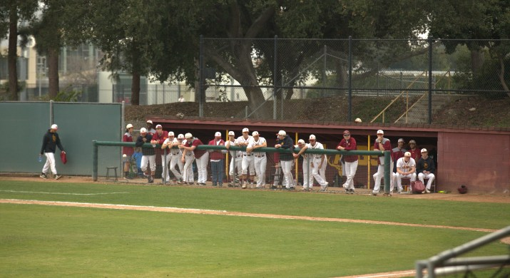 Several baseball players stand in a dugout in the background. A portion of the baseball field can be seen in the foreground.