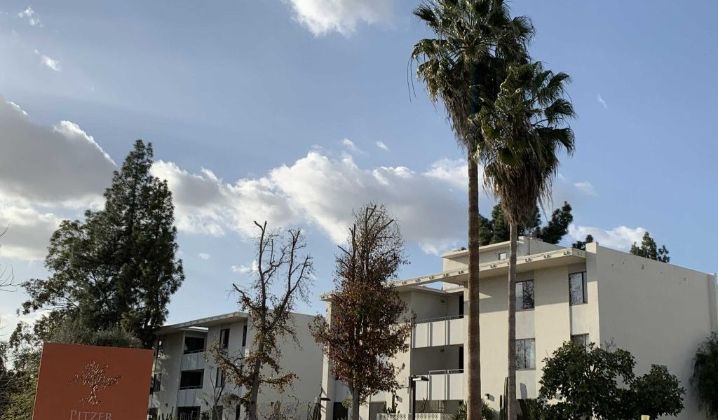 """A photograph of two Pitzer College buildings. They are both white and have three floors. In front of the buildings are several trees, and in the bottom left of the image is an orange sign that says """"Pitzer College Campus Map."""""""