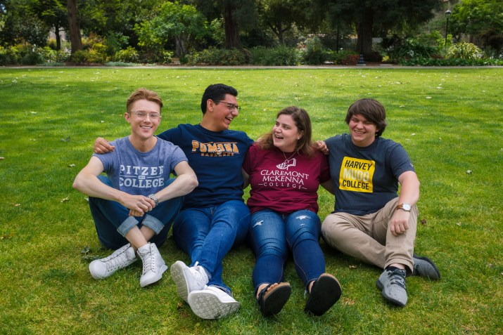 Four college students sit together on a green grass field laughing; they are the newly elected student body presidents of Pitzer, Pomona, Claremont McKenna, and Harvey Mudd Colleges. On the far left sits Clint Isom who wears a light blue Pitzer College t-shirt. Next to him is Miguel Delgado in a dark blue Pomona College t-shirt. Next sits Dina Rosin in a red CMC shirts and on the far right is Kyle Grace in a grey and yellow Harvey Mudd shirt.