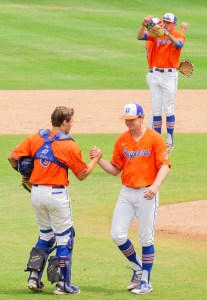 Two Sagehens give each other a firm handshake in the infield.