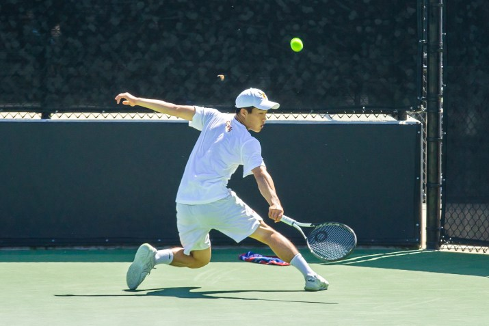 Robert Liu, and Asian male on the CMS tennis team hits a tennis ball, with his back to the camera, one arm outstretched, shoes skidding across the ground.