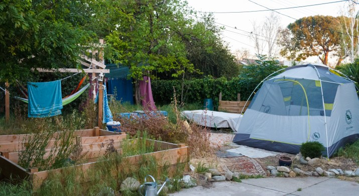 A backyard with a tent and garden