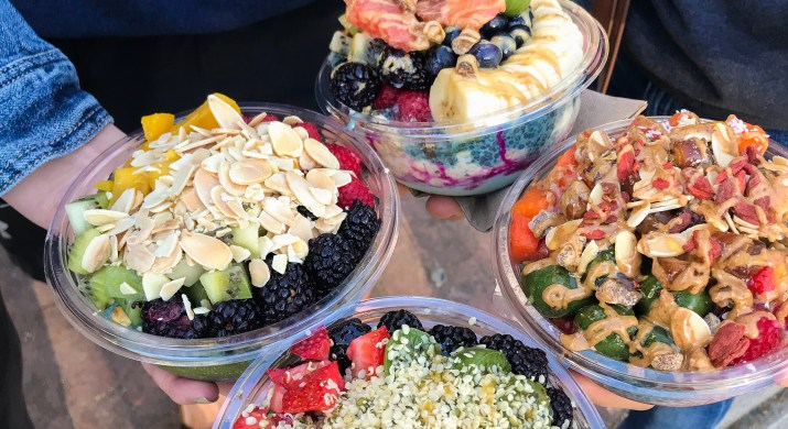 An image of four acai bowls, all of which are colorful and full. From bottom (going clockwise): topped with berries, kiwi berries and nuts; topped with kiwi, berries and sliced almonds; topped with banana, berries and honey; topped with fruit and almond butter.