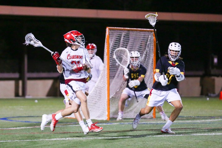 A lacrosse player carries the ball near the goal, looking to pass to a teammate. He wears a white jersey and a red helmet.