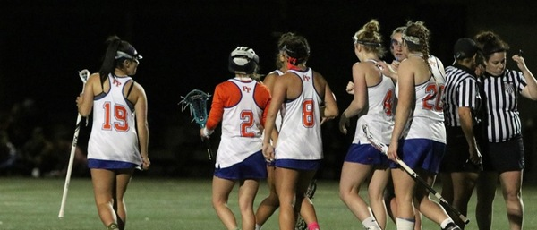A crowd of female lacrosse players with their backs to the camera walk off the field to the left, while referees talk to each other on the right side of the image.