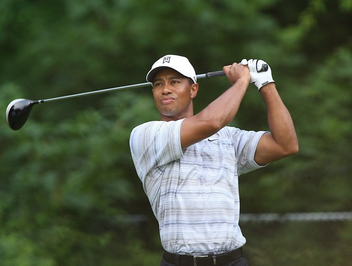 Tiger Woods, in a white shirt, swings a golf club with green trees in the background.