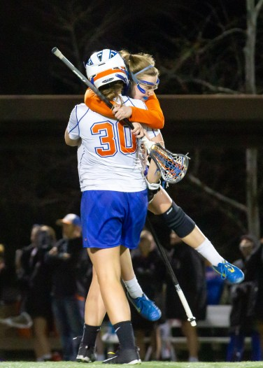 One player jumps up and hugs a teammate, both of her feet lifted off the ground.