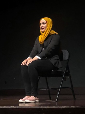 Sundeep Morrison in performance. She is sitting on chair and wearing a black jacket, black jeans, pink shoes and a yellow headscarf.
